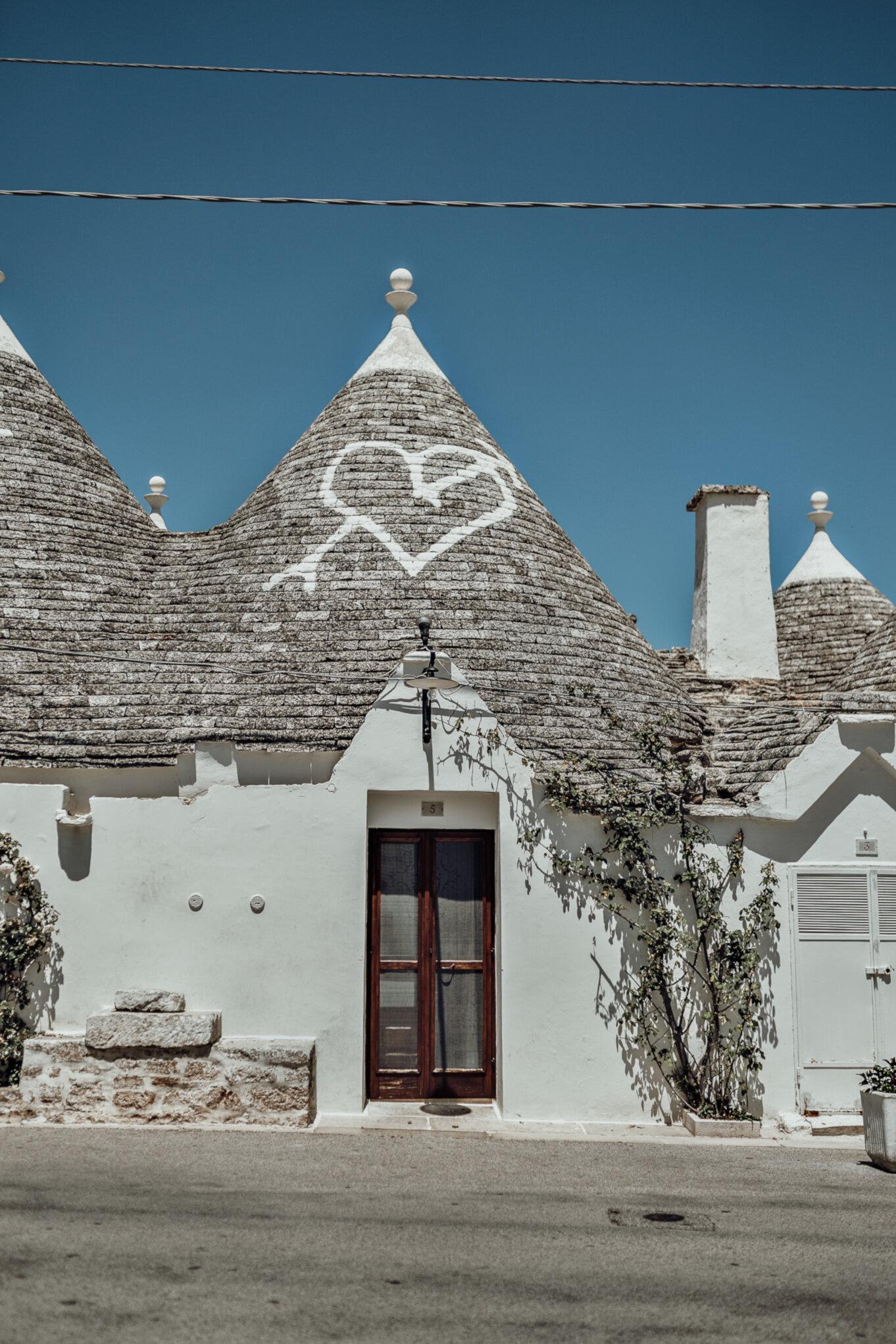 Domek trulli z symbolem serca przeszytego strzałą na dachu