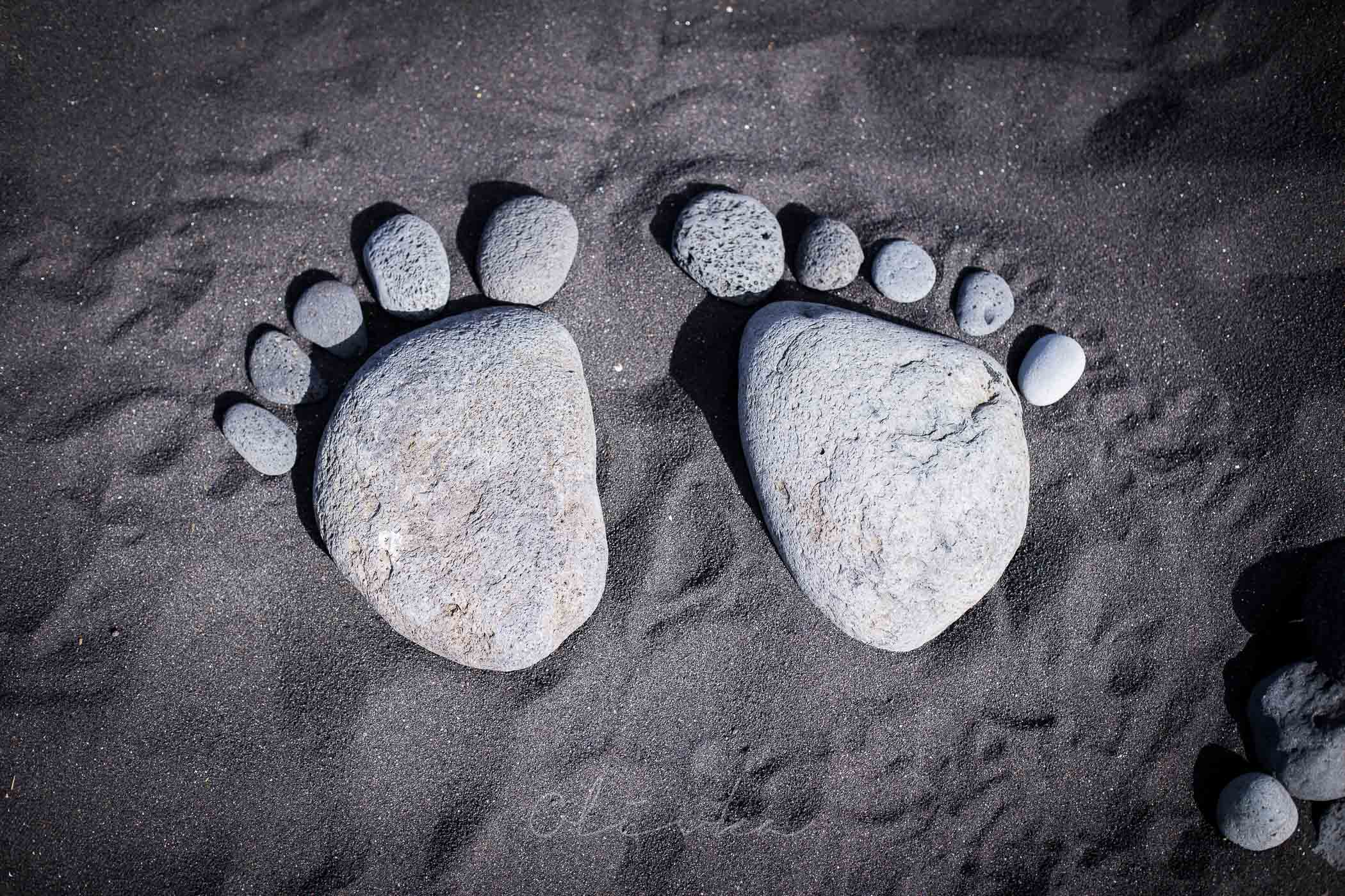 Ślady stóp ułożone z kamieni ma czarnym piasku