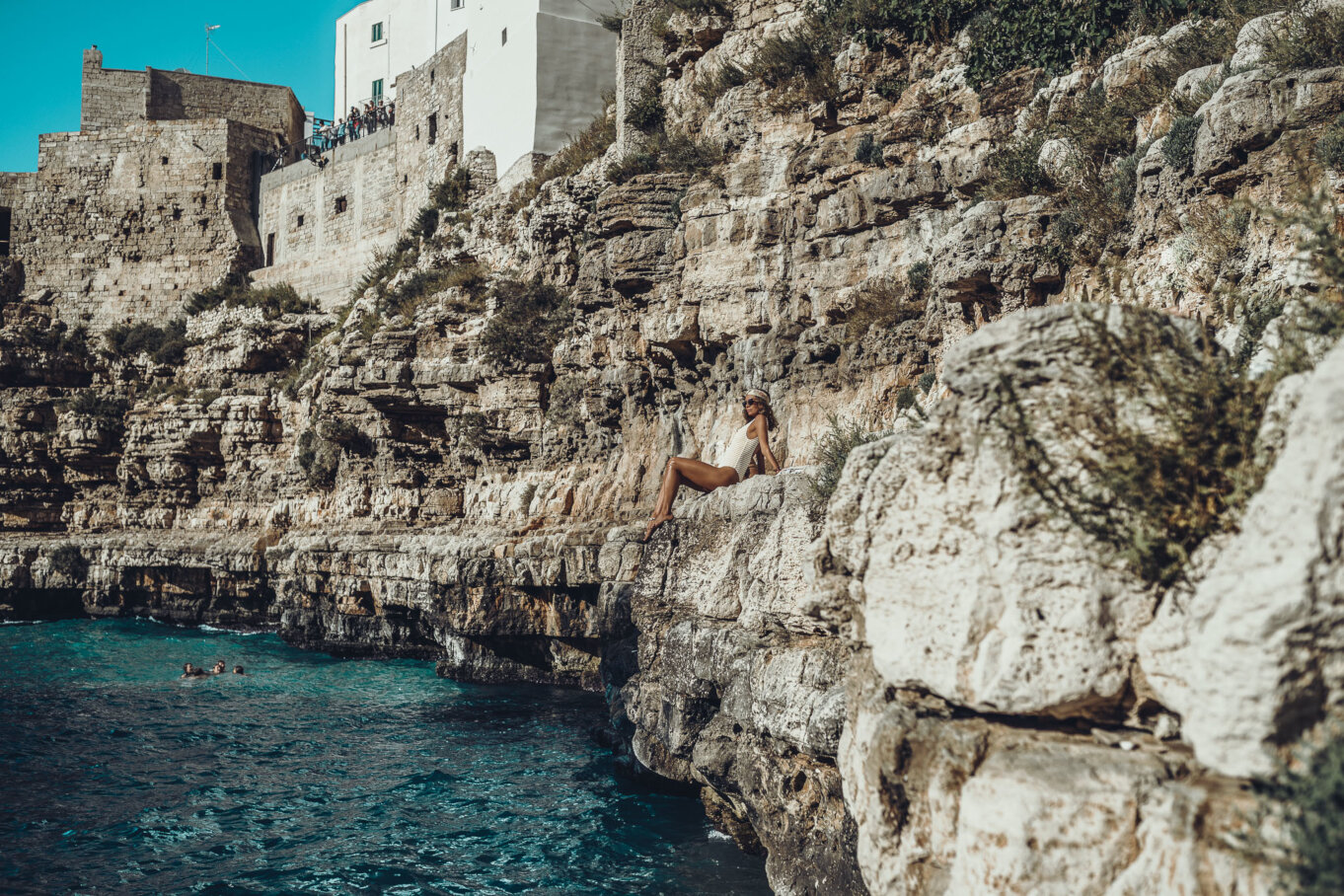 Opalanie na skalistym brzegu plaży w Polignano a Mare